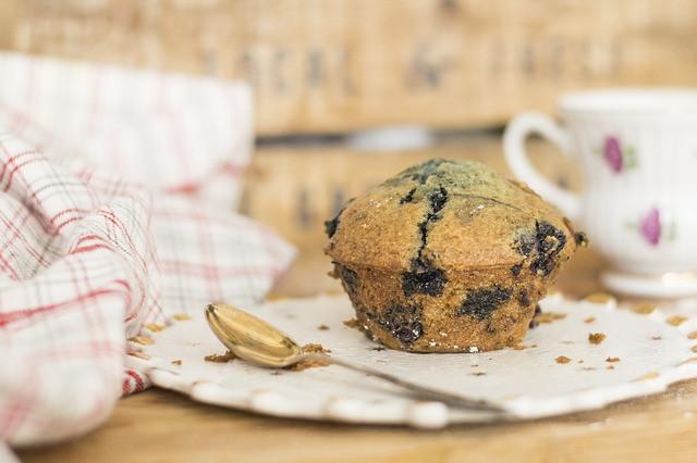 Einzelner Blaubeermuffin mit Kaffeetasse